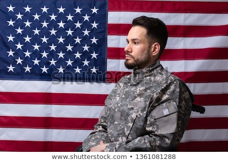 Stock photo: Veteran Sitting In Wheelchair In Front Of An American Flag