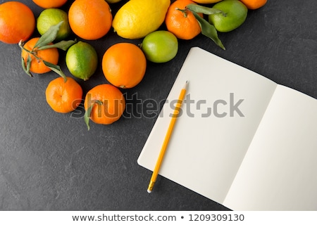 Stockfoto: Close Up Of Fruits And Notebook On Slate Table Top