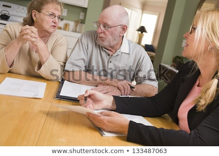 Senior Adult Couple Going Over Documents in Their Home with Agen Stock photo © feverpitch