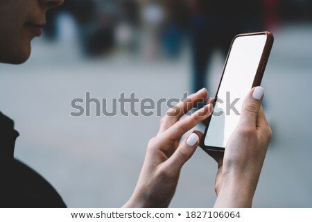 cropped image of young lady outdoors using mobile phone stock photo © deandrobot