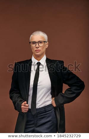 Young elegant woman in eyeglasses looking at you in fashion studio Stock photo © pressmaster