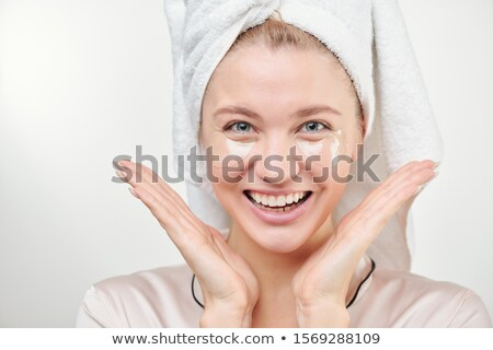 Young beautiful woman with under-eye patches looking at you with toothy smile Stock photo © pressmaster