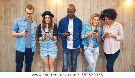 Group of young people staring on their phones Stock photo © Kzenon