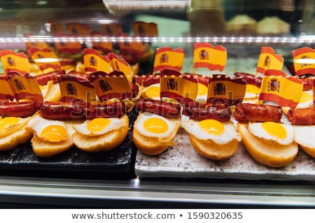 Spanish burger with omelet and souvenir flag of Spain in the market of San Miguel Stock photo © ruslanshramko