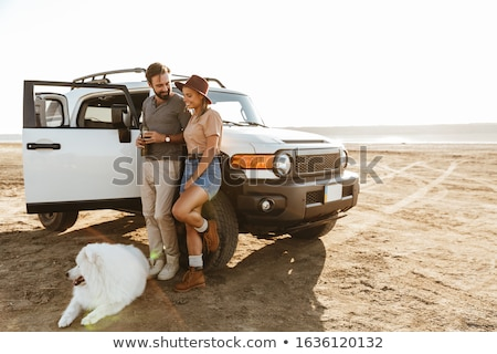 couple outdoors at beach walking with dog samoyed stock photo © deandrobot