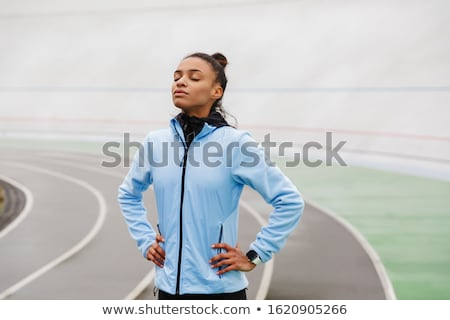 Attractive young african sportswoman resting after running stock photo © deandrobot