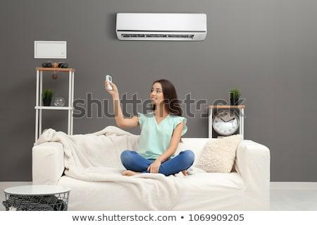 Climatiseur maison homme femme séance canapé Photo stock © AndreyPopov