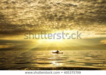 Pôr do sol mar silhueta caiaque laranja azul Foto stock © vapi