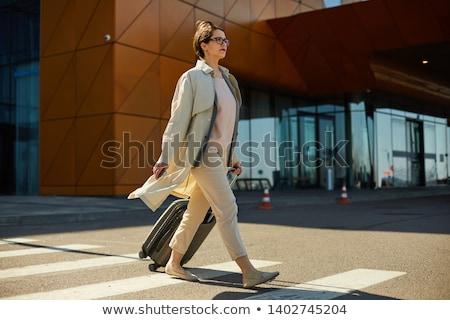 woman wheeling a suitcase stock photo © photography33