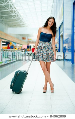 Young pretty stylish woman with luggage at the international air Stock photo © HASLOO