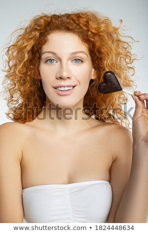 Attractive young brunette with chocolate heart. Stock photo © lithian