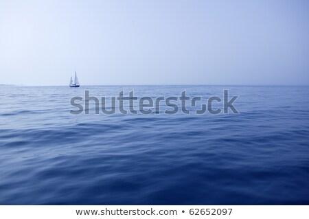 blue sea with sailboat sailing in a foggy coast stock photo © lunamarina