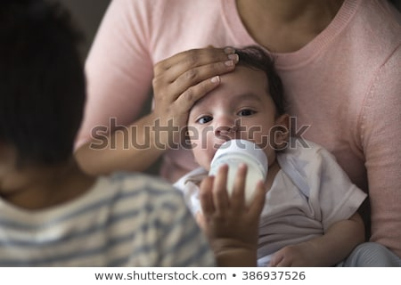 Close-up of a baby boy bottle-fed by his mother at home Stock photo © wavebreak_media