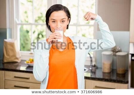 Woman drinking milk and flexing muscles Stock photo © wavebreak_media