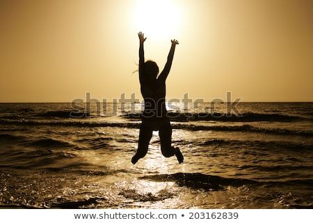 Young redhead girl jumping at the beach. Stock photo © Massonforstock