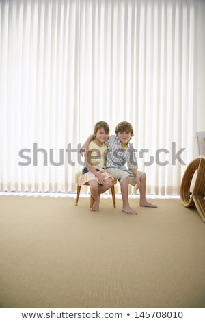 Сток-фото: Mixed Race Boy Sitting On Stool In Front Of Curtain