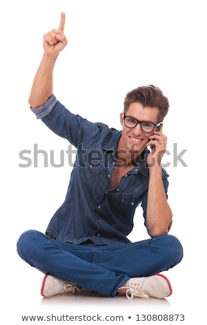 handsome man posing seated with legs crossed stock photo © feedough
