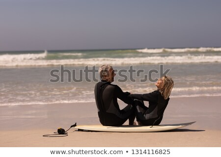 Side view of smiling senior man sitting on surfboard Stock photo © wavebreak_media