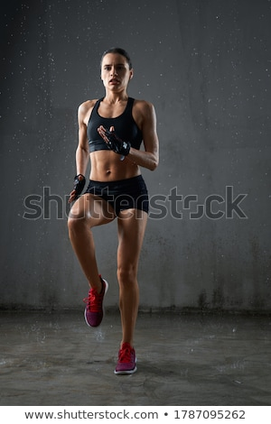 Full length portrait of a concentrated muscular sportswoman Stock photo © deandrobot