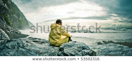 man in raincoat sitting at shore Stock photo © IS2