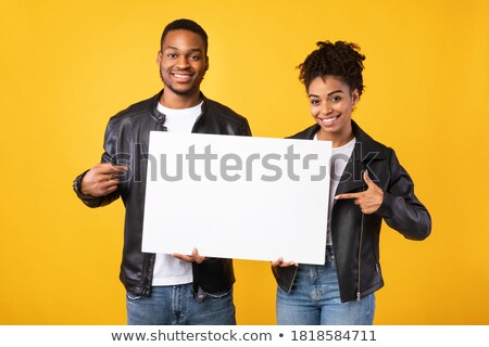 young casual couple recommending something on blank board  Stock photo © feedough