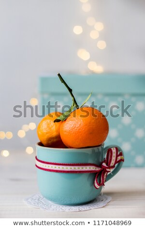 two fresh mandarins in a blue ceramic mug with a ribbon and tasty christmas candy on bokeh backgroun Stock photo © laciatek
