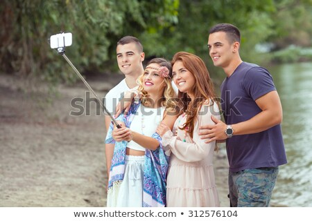 Photo of four hippie people men and women, smiling and taking se Stock photo © deandrobot