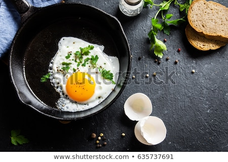 Fried eggs in a frying pan on a wooden background with copy space. Breakfast from natural fresh prod Stock photo © artjazz