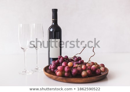 Luxury bottle of red wine and empty glasses with dark grapes inside vintage wooden box on black ston Stock photo © DenisMArt