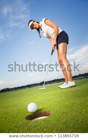 Happy girl golfer putting ball into hole. Stock photo © lichtmeister