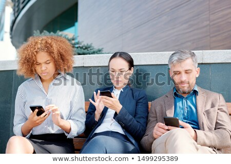 row of mobile employees sitting along wall and scrolling in their smartphones stock photo © pressmaster