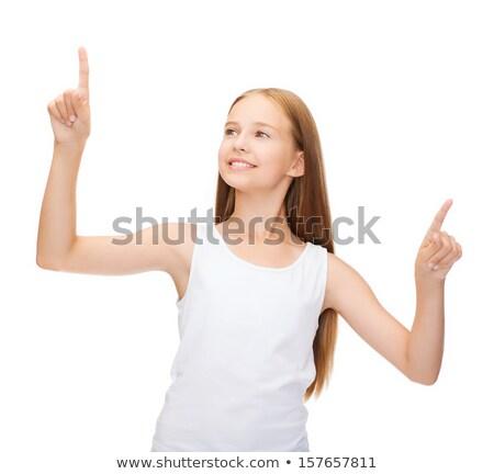 happy teenage girl pointing to something imaginary Stock photo © dolgachov