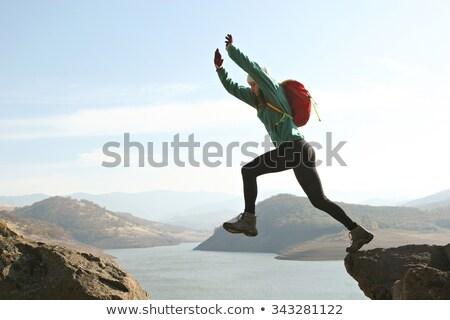 Aktif kadın atlama dağ gün batımı Stok fotoğraf © lovleah