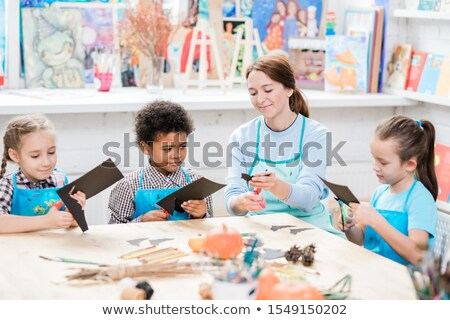 Intercultural schoolkids and their teacher in aprons cutting out halloween bats Stock photo © pressmaster