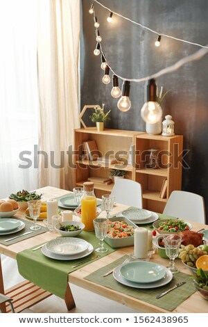 Festive table served for Christmas party with lamps hanging over meal Stock photo © pressmaster