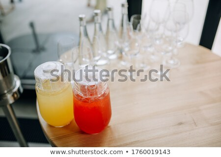 Lemon juice in glass and jug on white background Stock photo © bluering