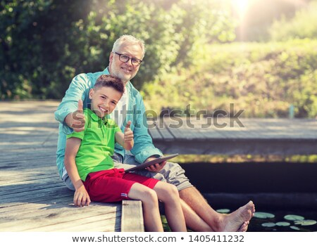 grandfather and boy with tablet pc on river berth Stock photo © dolgachov