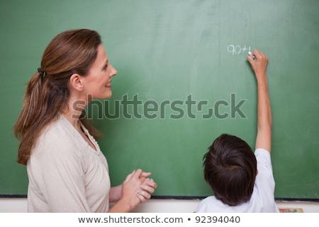 Happy schoolteacher helping a schoolboy doing an addition on a blackboard Stock photo © wavebreak_media