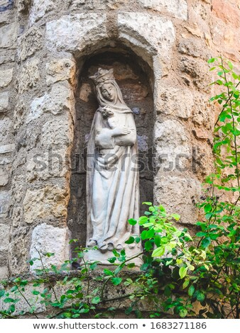 Old medieval stone statue in wall of Virgin mary with child  Stock photo © Hofmeester