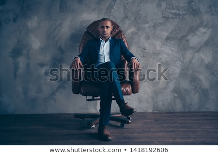 smart man wearing glasses sitting on a chair with legs crossed stock photo © feedough