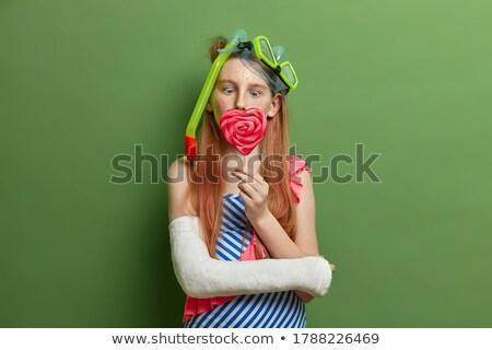 Gyömbér lány tart édes nyalóka színes Stock fotó © konradbak