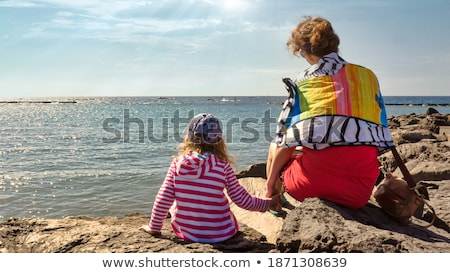 Parents with child sit on seacoast,  rear view Stock photo © Paha_L