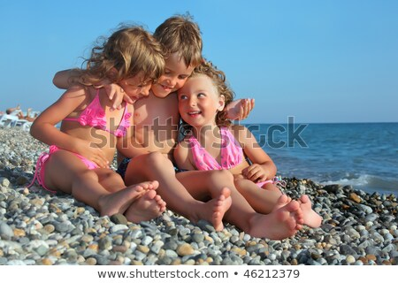 children three together sitting on stony beach stock photo © paha_l