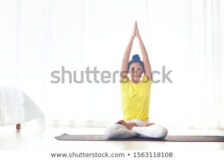 two women practicing yoga sitting in lotus pose on bed stock photo © deandrobot