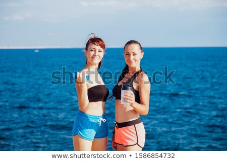 fitness girls with shaker and dumbbells on the beach stock photo © dmitriisimakov