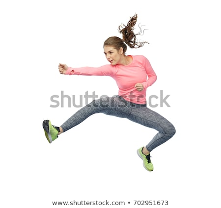 happy sporty young woman jumping in air stock photo © dolgachov