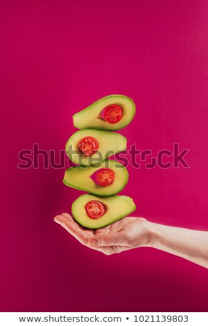 cropped shot of female hand holding levitating avocados isolated on pink Stock photo © LightFieldStudios