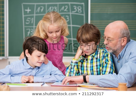 Schoolchildren and their teacher reading in primary class Stock photo © monkey_business