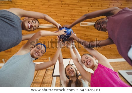 Low angle view of smiling high school kids holding basketball together in the court Stock photo © wavebreak_media