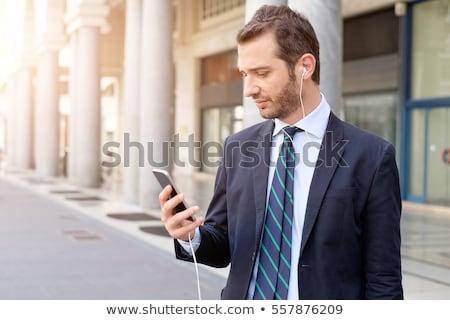 Férfi fülhallgató okostelefon sétál város emberek Stock fotó © dolgachov